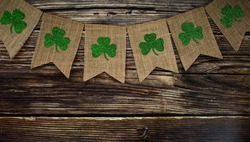 Background for St. Patrick's Day, March 17, with a festive garland of clover on a wooden background. Copy of the text space.