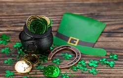 Background for St. Patrick's Day, March 17, with a lucky horseshoe, a leprechaun hat, a clover and a pot of gold on a wooden background.