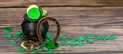 Background for St. Patrick's Day, March 17, with a lucky horseshoe, clover and a pot of gold on a wooden background.