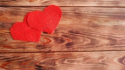 background for valentine's day card. hearts of red canvas on a wooden background