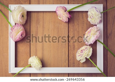 Background for wedding or party invitation. Picture frame with flowers on wooden table. View from above