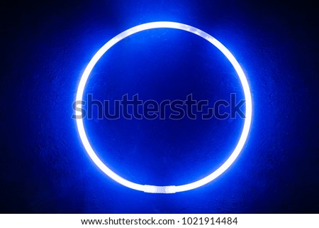 Background from a round glow stick of blue color like neon on a black board #1021914484