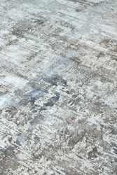 Background from a stylish carpet in neutral gray-beige-blue tones with fading and artificial antiquity effect. Concept details of a fashionable interior, carpets. Abstract texture. Vertical.