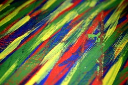 Background from different strokes of red, yellow, green and blue paint brush close-up. Bright colorful backdrop of colored brush lines. Mixing color streaks of paint. Focus - center, edges - blurry
