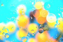 Background from multi-colored large balls of heterogeneous coloring, mainly blue, interspersed with orange and yellow tones, texture, blur, close-up