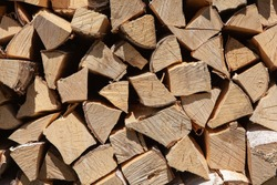 Background from stack of firewood from birch tree, for heating house, stacked in backyard, uncut wood, birch. Concept eco-friendly home heating during cold season. Overall plan. Horizontal format.