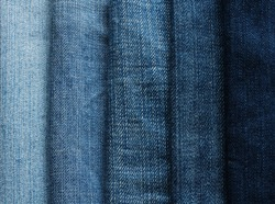 background from strips of fabric of blue jeans of different shades and brightness