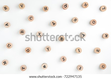 Background from the letters of the English alphabet on wooden cylinders. Stamps. Background for your text and design                                 #722947135