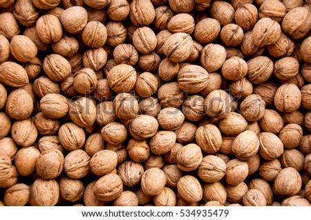 Shutterstock Background from walnuts. Nuts background closeup. Natural organic food.  Assortment of walnuts.  Whole walnuts and nutcracker background. Top view. Harvest concept.