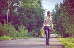 background girl standing turned her back on urban asphalt road  among trees and tall grass outside the town