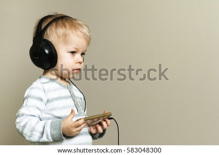 Background Half profile of  two years old boy heeds in to the sounds of music in headphones, holding in hands the smartphone. #583048300