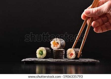 Background hands picking four assorted vegetable maki sushi with chopsticks on slate serving plate on dark wooden table with black background. Front view. Horizontal composition.