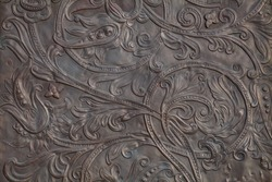 Background image - a floral pattern in the form of embossing on metal