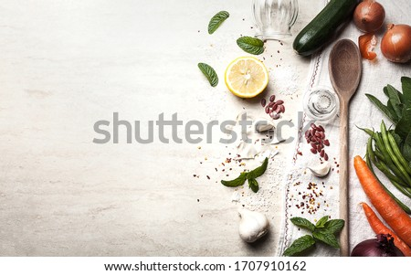 Background image, food-themed, in which the right half presents a composition of vegetables with a wooden ladle and a dish towel, while the left half is left available for any content and announcement