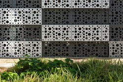 Background image of a perforated facade with a green foreground