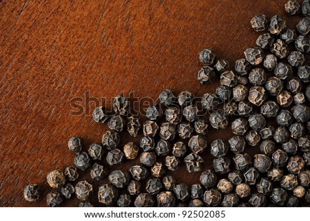 Background image of black peppercorns on  dark wood cutting board with copy space.  Macro with shallow dof.