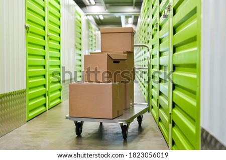 Background image of cart with cardboard boxes in empty hall of self storage facility, copy space Stock photo ©