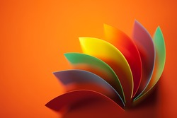 background image of colorful origami fan pattern made of curved sheets of paper, on orange background