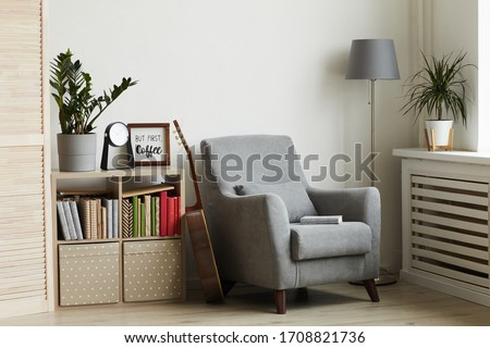 Background image of cozy reading nook in modern minimal interior, focus on grey armchair against white wall, copy space Foto d'archivio ©