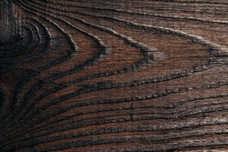 Background image of dark wood texture. Lacquered board with a large pattern of fibers for construction and finishing works, furniture production. Texture element.