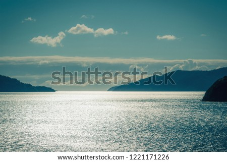 Background image of glistening water on the sea between islands of the Marlborough Sounds in New Zealand.