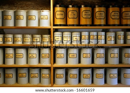 Background image of old pharmaceutical canisters used in creating medicine. Shot with ambient room lighting.