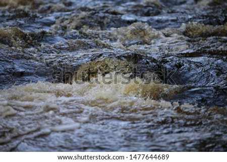Background image of the water of Karelia. Underwater rapids of a river with a fast flow and a swirl pattern. Swirling whirlpools. A water game with splashes and foam. The element of nature. Selective  #1477644689
