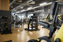 Background image of various exercise machines in workout hall of modern gym interior, copy space