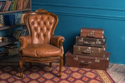 Background image of vintage old room with a bookshelf, leather and wooden armchair in classic style, colorful antique carpet and a lot of suitcases with blue wall. Copy space. Vogue and luxury.