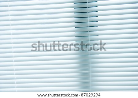 background image of white mini blinds inside home closed.