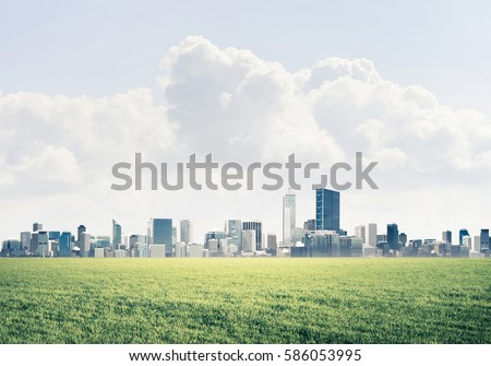 Background image with modern cityscape blue sky and green spring field #586053995