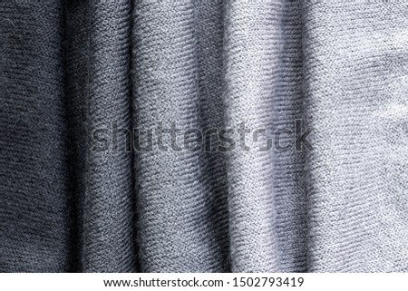 Background in the form of a wool product with vertical lines and with a gradient from dark gray to light gray