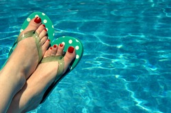 Background is filled with aqua water.  Woman has on polka dotted flip flops and has red painted toe nails.  Feet only.