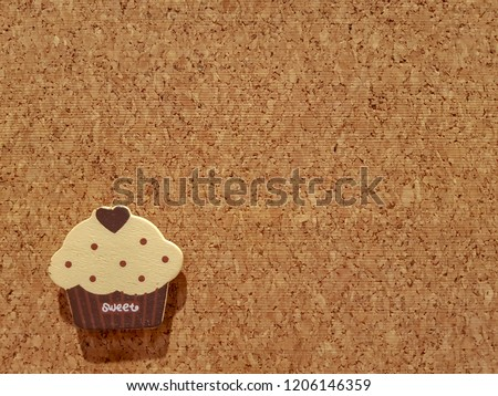 Background is Medium Density Fiberboard is engineered wood wallboard made of wood chips and other recycled materials and copy space right side to put text and pictures on demand and has Cupcake shape.