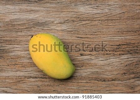 Background: isolated ripe mango on the wooden table
