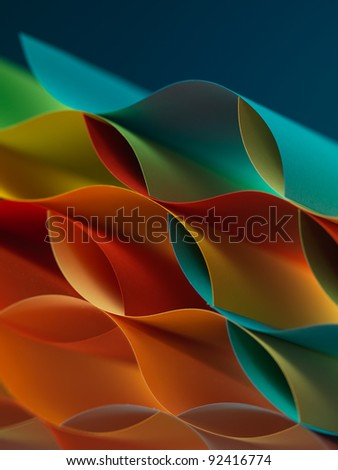 background macro image of colored origami pattern made of curved sheets of paper, with mirror reflexions