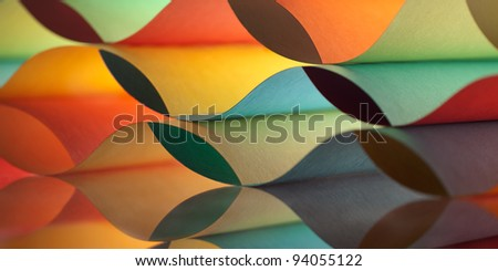 background macro image of colorful origami pattern made of curved sheets of paper, with mirror reflexion