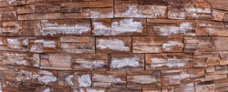 Background Modern building facade made of decorative stone, panorama. Brick or stone wall texture, banner. Fungus and mold on the stones.