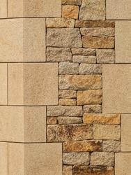 Background natural stone masonry with granite corner stones