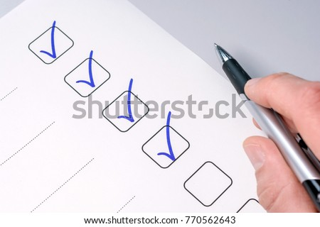 Background of a checklist with checked tasks and a pen-holding hand