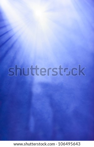 Background of a radiating bright white light source in a blue hazy sky caused either by the suns rays penetrating thin cloud or by a floodlight at an open-air event in a smoky atmosphere