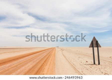 background of a red sandy desert road in the Namib and the backside of a warning triangle road sign, Skeleton coast National Park, Namibia, Africa
