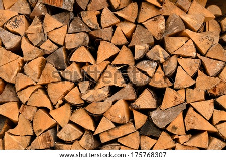 Background of a stack of split logs in a woodpile for use as domestic heating in winter with a close up view of the cross-section at the ends