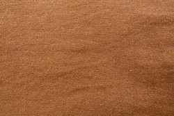 Background of a textured brown cotton fabric.