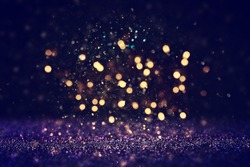 background of abstract glitter lights. blue, gold and black. de focused