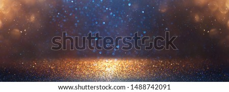 Photo of  background of abstract glitter lights. blue, gold and black. de focused. banner