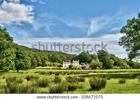 Background of an English country house nestling in lush green countryside under a blue summer sky