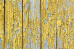 Background of an old wooden house with old yellow paint. Peeling paint reveals the wood texture