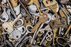 Background of assorted old multi-colored metal antique keys of different shapes. Home security concept.