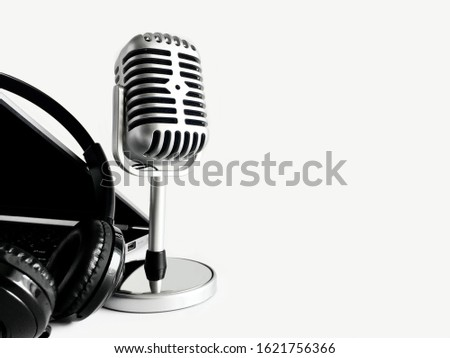 Background of audio equipment on the left side of the light gray background, including a retro microphone, a headphones and a laptop.